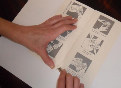 Abrir ao meio o livro e levantar os agrafes.