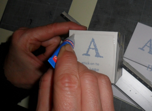 Por cola na base do cubo que tem uma letra.